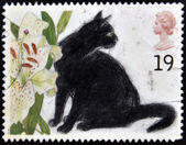 UNITED KINGDOM - CIRCA 1995: A stamp printed in England, shows the Black cat and Lilium, circa 1995 — Stock Photo