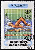 Madagascar - circa 1994: un sello impreso en madagascar dedicada a los deportes de verano muestra natación, circa 1994 — Foto de Stock