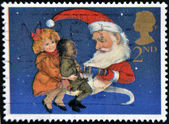 UNITED KINGDOM - CIRCA 1997: A stamp printed in Great Britain showing Children and Father Christmas pulling a Christmas Cracker, circa 1997 — Stock Photo