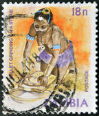 ZAMBIA - CIRCA 1981: A stamp printed in zambia shows millet grinding on a stone, circa 1981 — Foto Stock