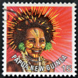 PAPUA NEW GUINEA - CIRCA 1977: stamp printed in Papua New Guinea shows a woman in a feathered headdress from the area near Koiari, circa 1977 — Stock Photo