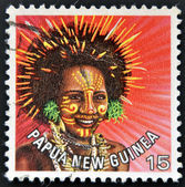 PAPUA NEW GUINEA - CIRCA 1977: stamp printed in Papua New Guinea shows a woman in a feathered headdress from the area near Koiari, circa 1977 — Stok fotoğraf