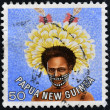 PAPUA NEW GUINEA - CIRCA 1977: stamp printed in Papua New Guinea shows a man in a feathered headdress from the area near Koiari, circa 1977 — Stock Photo