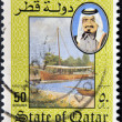 QATAR - CIRCA 1984: A stamp printed in Qatar shows a portrait of Sheikh Khalifa bin Hamed Al-Thani and landscape with boat, circa 1984 - Stockfoto