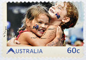 AUSTRALIA - CIRCA 2011: A stamp printed in australia shows embrace of friendship between two girls with the Australian flag in the face, circa 2011 — Stock Photo