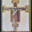 Stock Photo: AJMAN - CIRC1972: stamp printed in Ajman, Christmas collection, peace in world, shows painting of crucifixion of Christ by Master gave St. Francis , circ1972