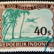 INDONESIA - CIRCA 1947: A stamp printed in Indonesia shows a airplane and palm trees, circa 1947 — Stock Photo