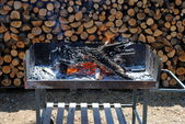 Barbecue grill with flames and wood on background — Stock Photo