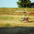 Colorful hang glider takes off in  farmland landscape — Stock Photo