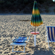 Beach umbrella and sunbed over sand at the sunset — Stock Photo #12381653
