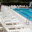 Stock Photo: Limpid swimming pool and white sunbeds without