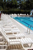 Limpid swimming pool and white sunbeds without — Stock Photo