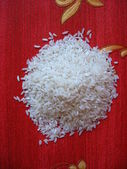 Scattered rice on a red background — Stock Photo