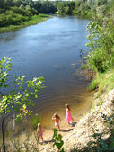 Three little girls plays at the river — Stock Photo
