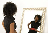 Lady looking at herself in mirror smiling — Stock Photo