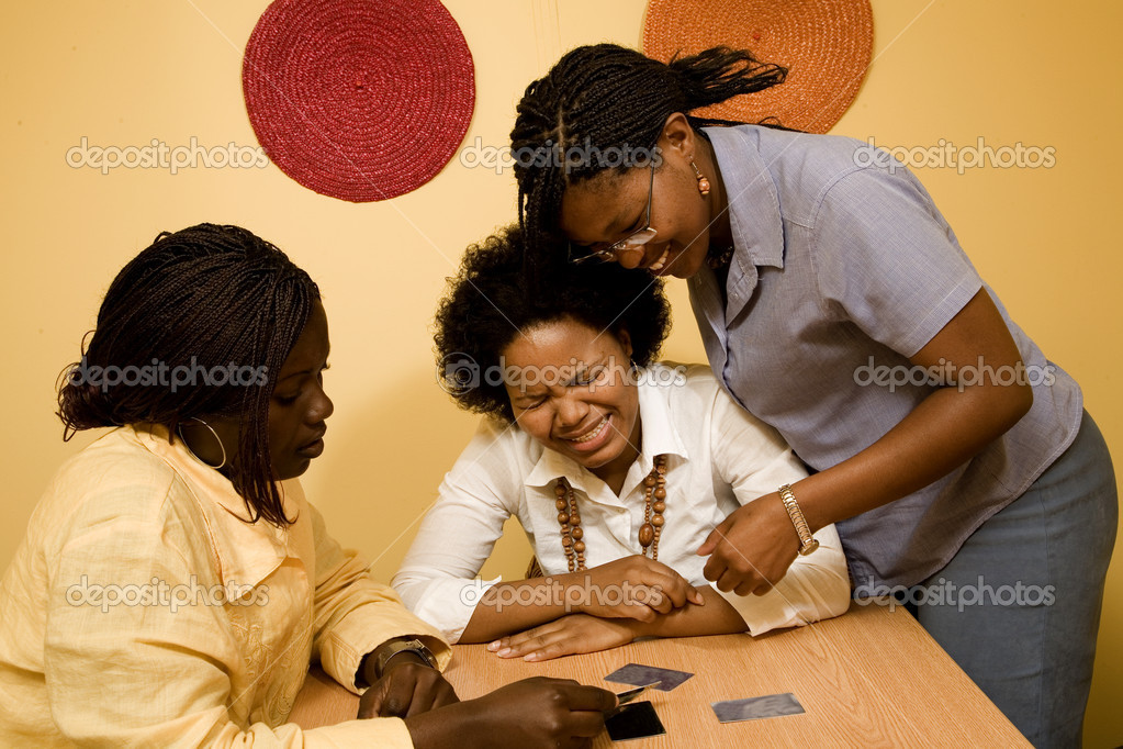 3 African women sitting at a table in discussion. Credit cards are on the table in front of them. One lady seems upset. — Stock Photo #11357717