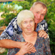 Smiling senior couple embracing outdoors — Stock Photo