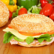 Fresh bagel with turkey breast, cheese, salad and tomatoes — Stock Photo