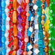 Lot of colored beads from different minerals and stone backgroun — Stock Photo #11379901