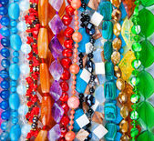 Lot of colored beads from different minerals and stone backgroun — Stock Photo