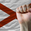 Royalty-Free Stock Photo: Us state flag of alabama with hard fist in front of it symbolizi