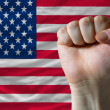 Royalty-Free Stock Photo: American national flag with hard fist in front of it symbolizing