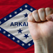 Royalty-Free Stock Photo: Us state flag of arkansas with hard fist in front of it symboliz