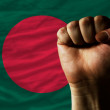 Hard fist in front of bangladesh flag symbolizing power - Foto Stock