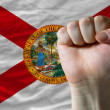 Us state flag of florida with hard fist in front of it symbolizi — Stock Photo