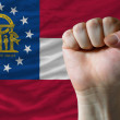 Us state flag of georgia with hard fist in front of it symbolizi — Stock Photo