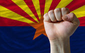 Us state flag of arizona with hard fist in front of it symbolizi — Stock Photo