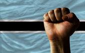 Hard fist in front of botswana flag symbolizing power — Stock Photo