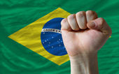 Hard fist in front of brazil flag symbolizing power — Stock Photo