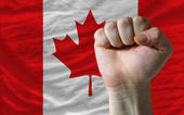Hard fist in front of canada flag symbolizing power — Stock Photo