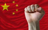 Hard fist in front of china flag symbolizing power — Stock Photo