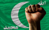 Hard fist in front of comoros flag symbolizing power — Stock Photo