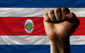 Hard fist in front of costa rica flag symbolizing power — Stock Photo