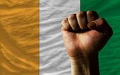Hard fist in front of ivory coast flag symbolizing power — Stock Photo