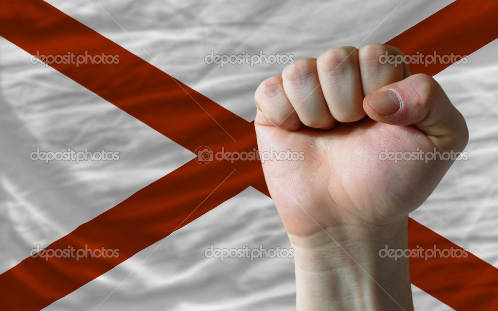 Complete american state of alabama flag covers whole frame, waved, crunched and very natural looking. In front plan is clenched fist symbolizing determination — Stock Photo #10994782