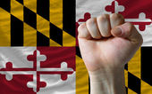 Us state flag of maryland with hard fist in front of it symboliz — Stock Photo