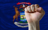Us state flag of michigan with hard fist in front of it symboliz — Stock Photo