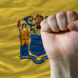Us state flag of new jersey with hard fist in front of it symbol — Stock Photo