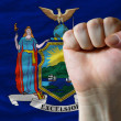 Us state flag of new york with hard fist in front of it symboliz — Stock Photo