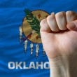 Us state flag of oklahoma with hard fist in front of it symboliz — Stock Photo