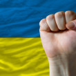 Hard fist in front of ukraine flag symbolizing power — Stock Photo
