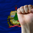 Us state flag of vermont with hard fist in front of it symbolizi - Stock Photo