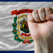 Us state flag of west virginia with hard fist in front of it sym - Stock Photo