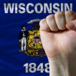 Us state flag of wisconsin with hard fist in front of it symboli - Stock Photo