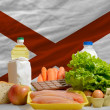 Basic food groceries in front of alabama us state flag — Stock Photo