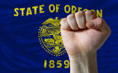 Us state flag of oregon with hard fist in front of it symbolizin — Stock Photo